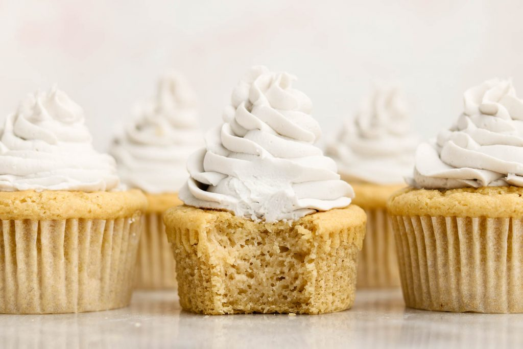 vegan gluten free vanilla cupcakes lined up beside each other with a bite in the middle cupcake