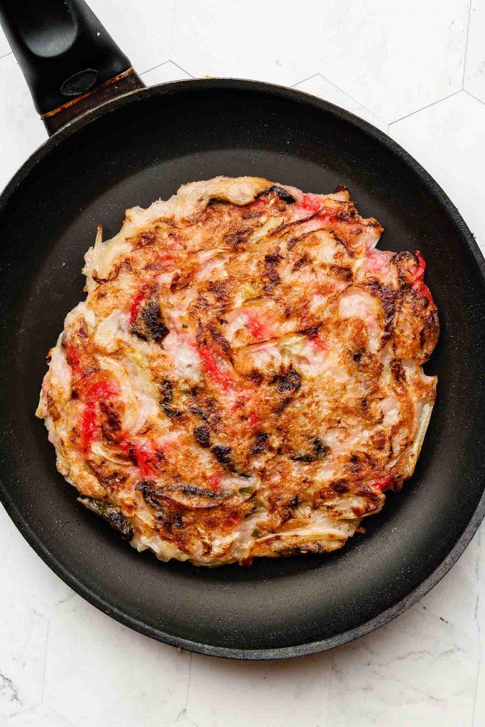 savory pancake on top of a large flat griddle pan