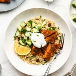 quinoa in a white bowl with tandoori tempeh, cucumber salad, yogurt and lemon