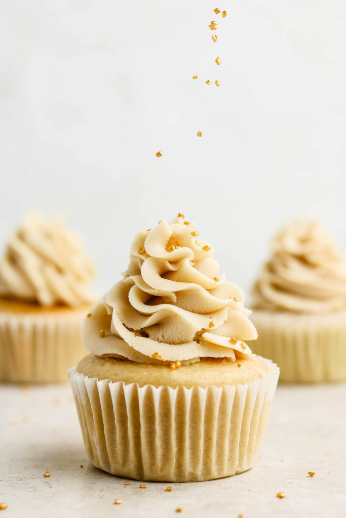 vanilla cupcakes with gold sprinkles on top