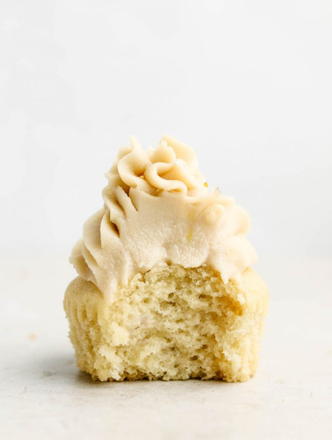 single fluffy vanilla cupcake with a bite taken out of it