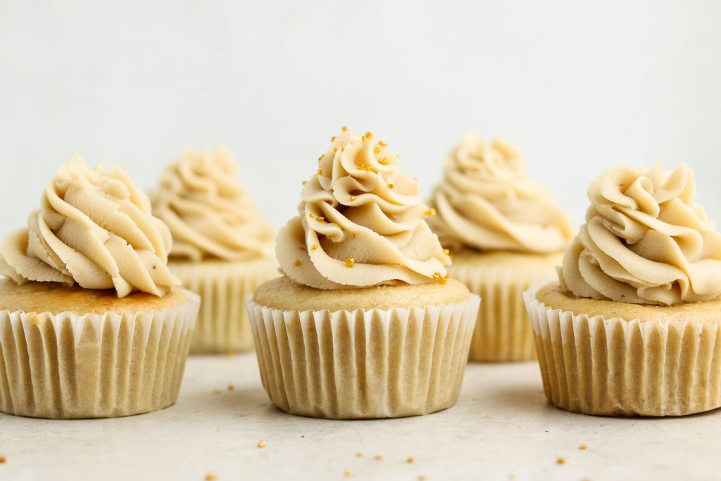 vanilla cupcakes with cashew frosting and gold sprinkles lined up