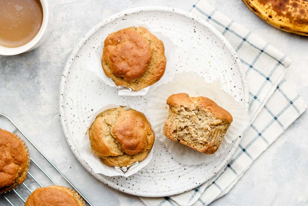 banana muffins on a speckled white plate on top of a checkered kitchen towel