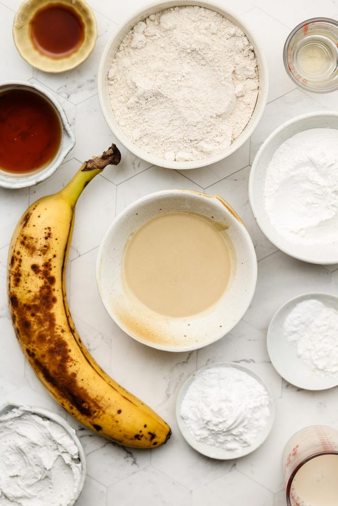 gluten free banana muffin ingredients in bowls on a marble back drop