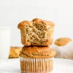 super fluffy gluten free banana muffins stacked with a bite taken out of the top muffin