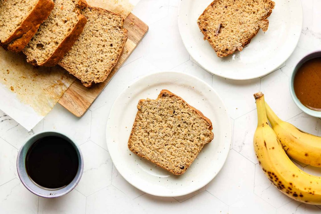slices of healthy banana bread on white speckled plates with coffee on the left side and bananas on the right side