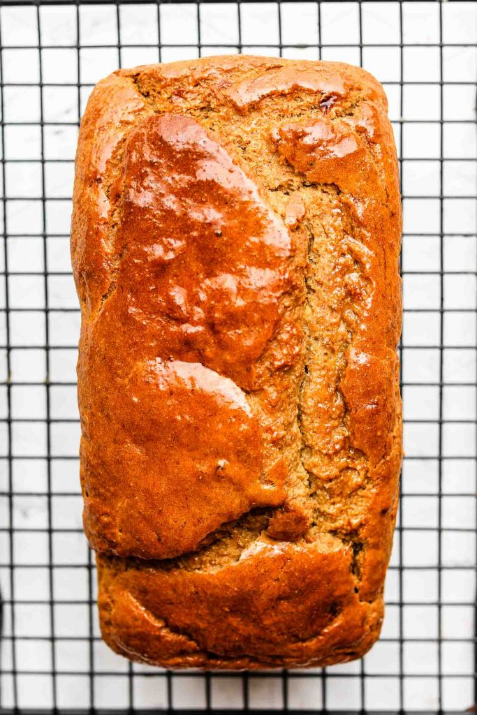 banana bread on a cooling rack with maple syrup on top