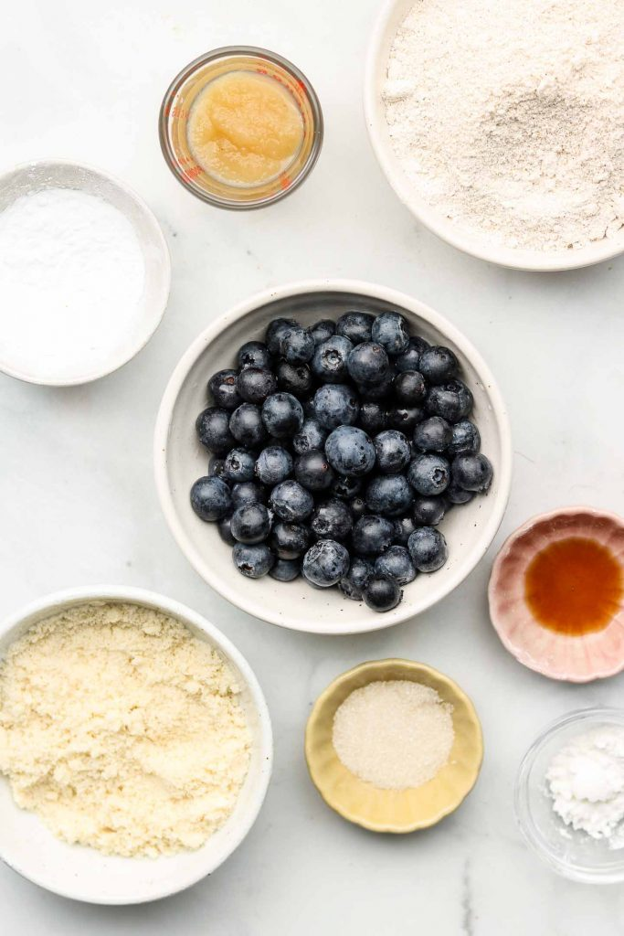 blueberry galette ingredients in white bowls on top of a blue backdrop