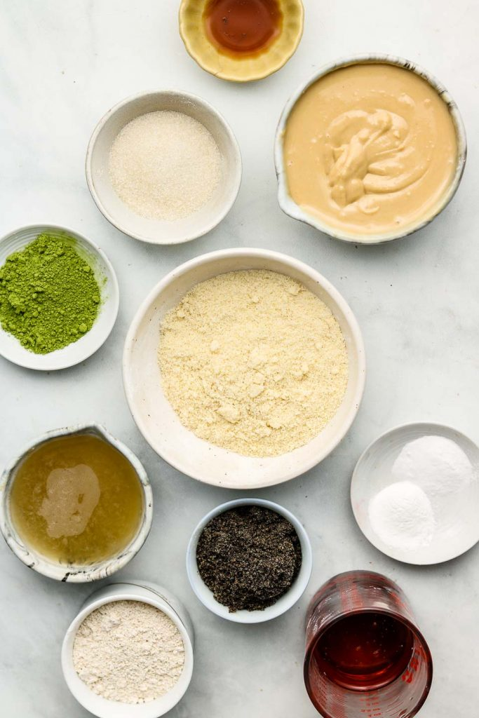 ingredients for matcha black sesame cookies in bowls on a marble blue backdrop