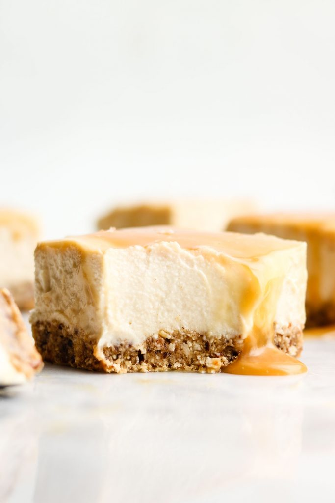 side shot of no bake salted caramel cheesecake with a bite taken out of it with a spoon