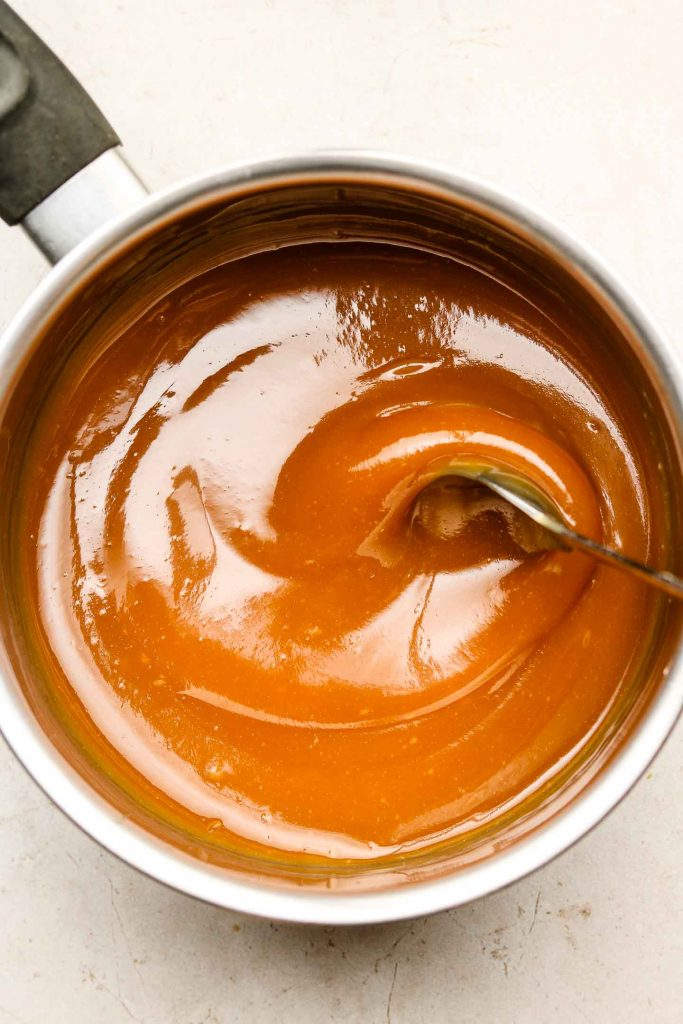 caramel sauce on a sauce pan being mixed with a spoon