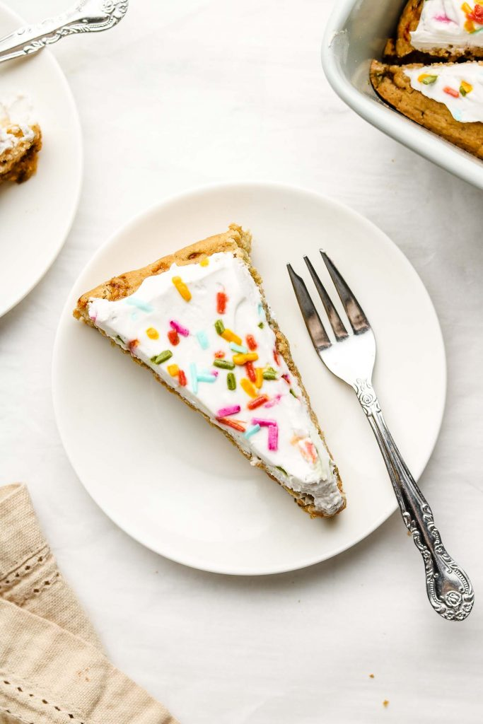 funfetti cake with vegan whip cream and sprinkles on top on a white plate and fork