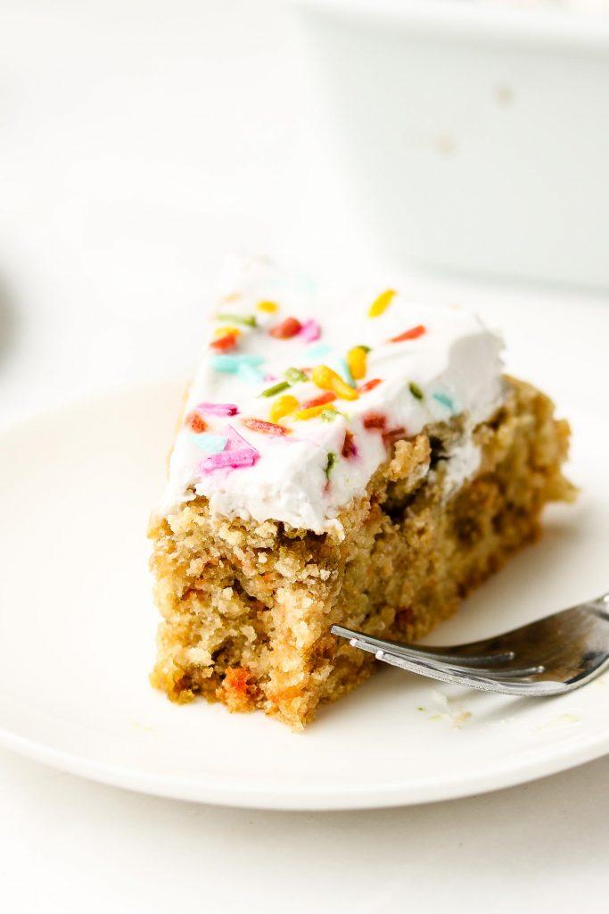 bite shot of vegan funfetti cake on a white plate