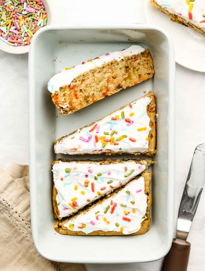 vegan funfetti cake cut into triangle slices in a blue loaf pan