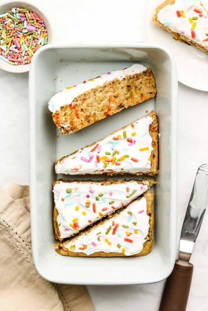 vegan funfetti cake cut into triangle slices in a blue loaf pan