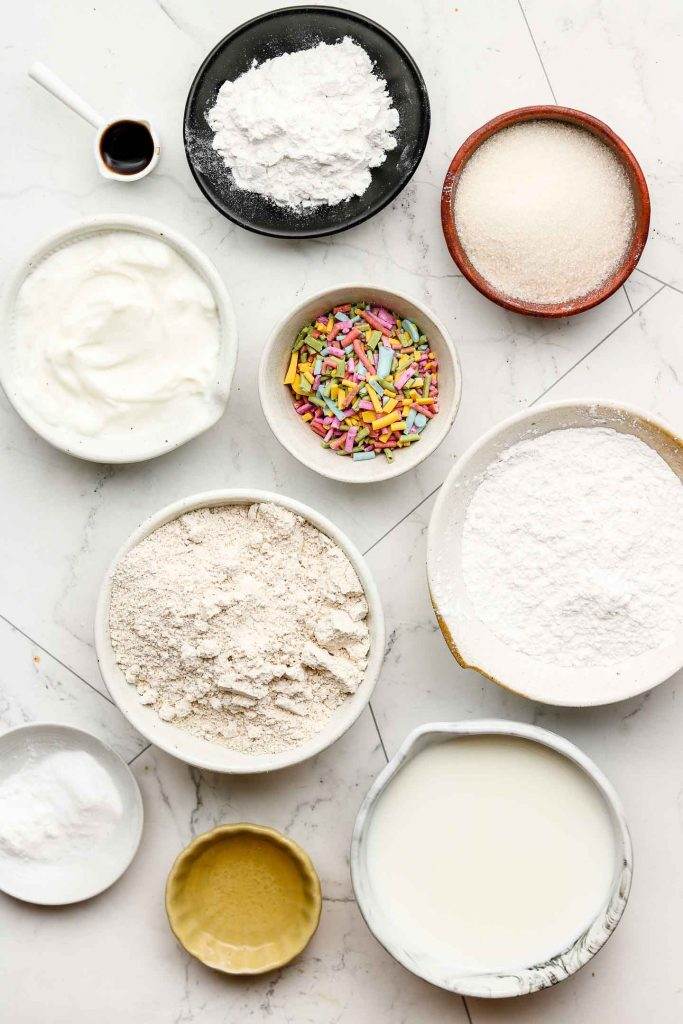 ingredients for vegan funfetti cake in bowls on a marble back drop