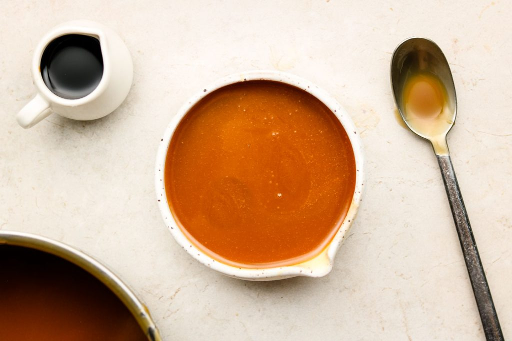vegan caramel sauce in a white speckled pour bowl with soy sauce on the left corner and spoon on the right corner