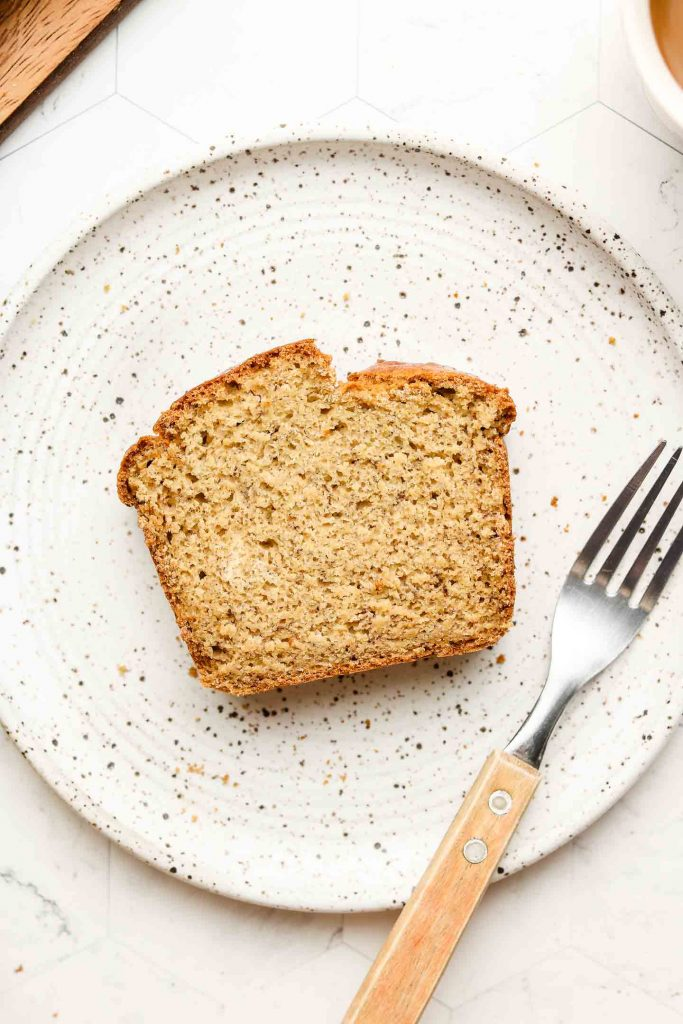 fluffy banana bread on a white speckled plate with a fork on the right side