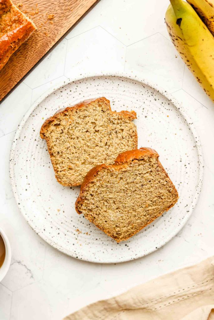 two pieces of fluffy banana bread on a white speckled plate with bananas in the corner