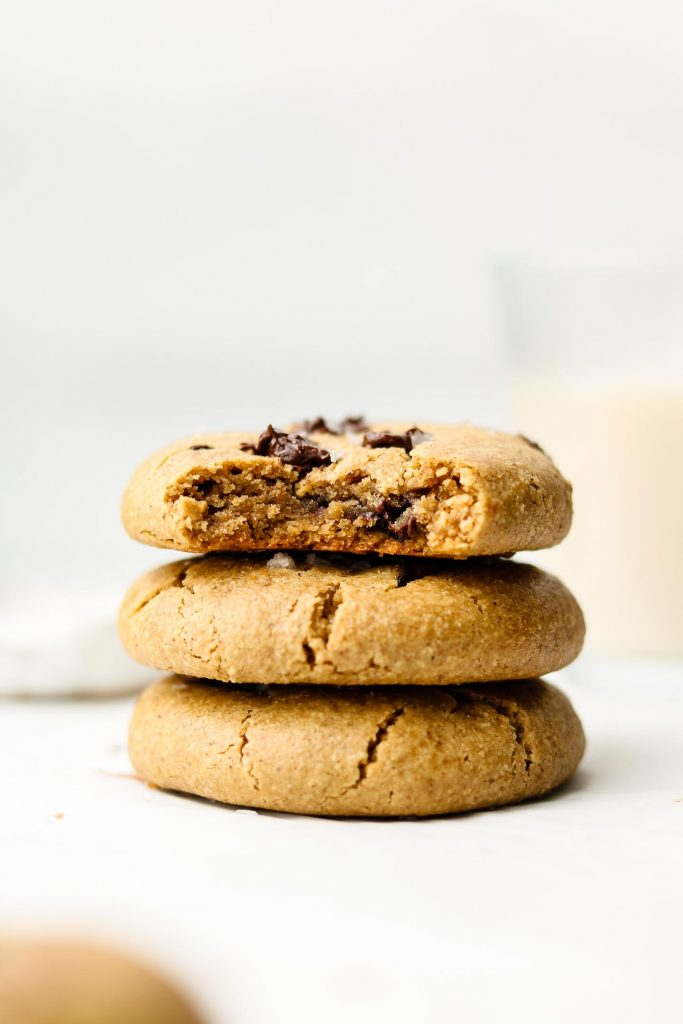 3 thick and chewy vegan chocolate chip cookies stacked on each other with milk in the background