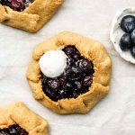3 mini blueberry galettes on parchment paper with coconut ice cream on top
