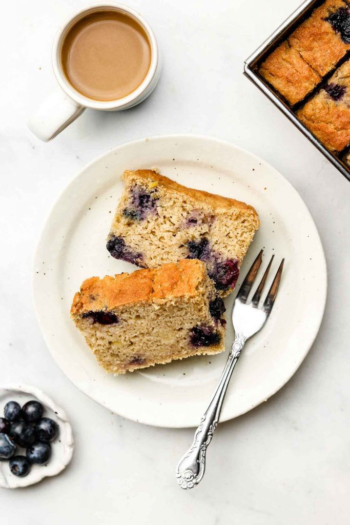 two slices of lemon blueberry loaf on a plate with a fork and coffee on the top left corner