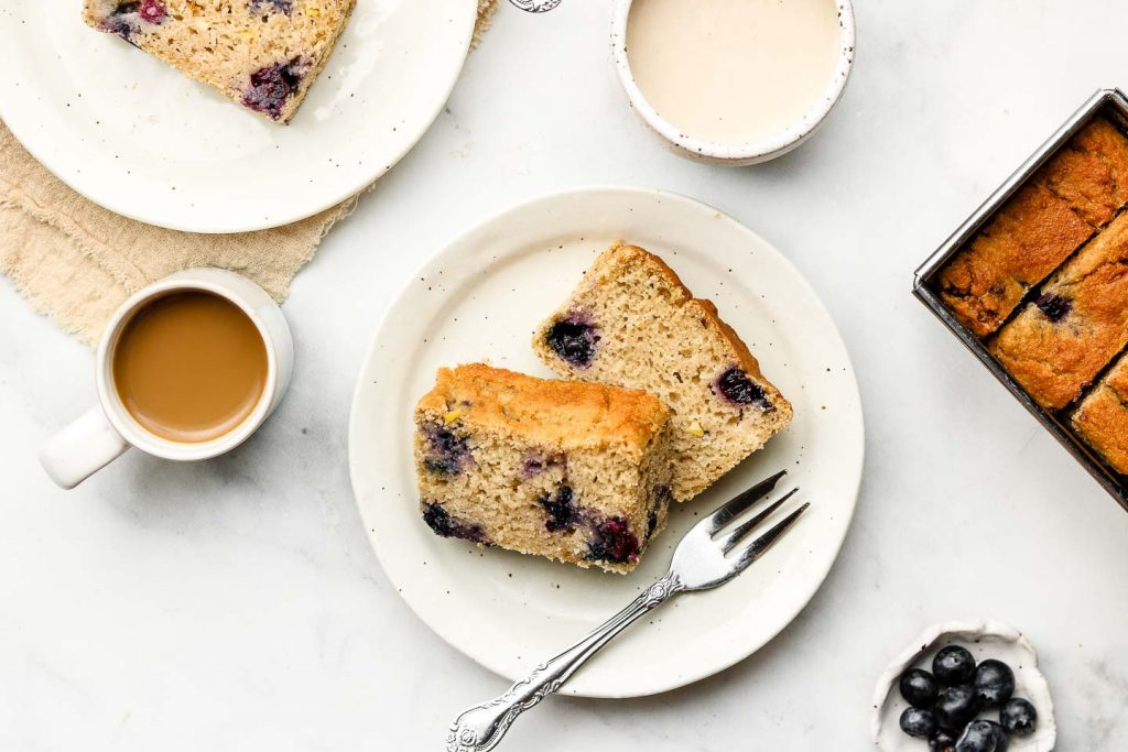 vegan blueberry lemon bread on a white plate with a fork and loaf pan beside it