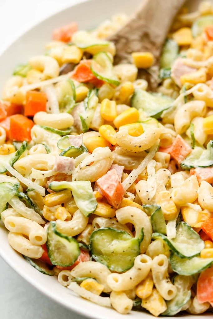 close up shot of macaroni pasta salad with cucumbers, carrots and corn