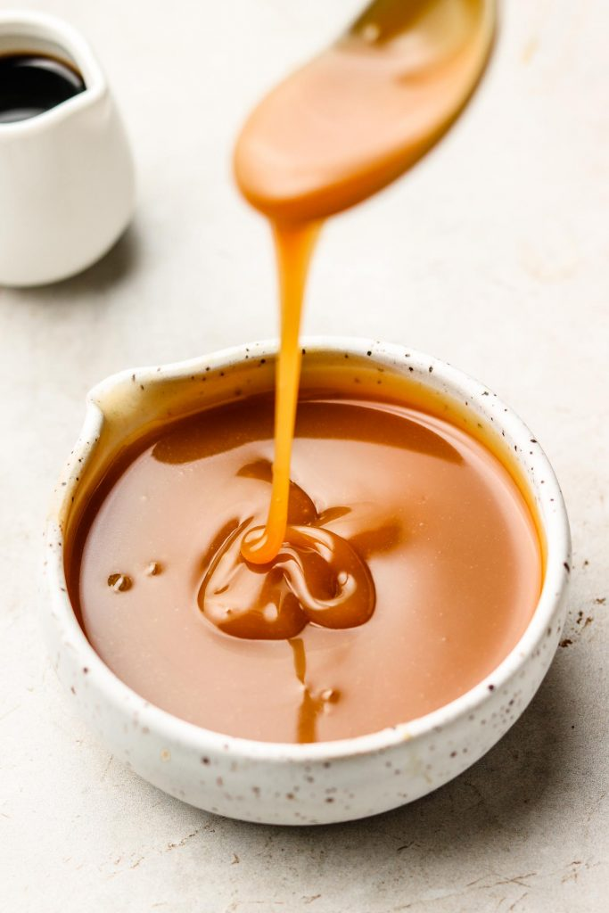 drizzling salted caramel sauce in a speckled white bowl