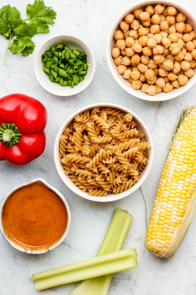 bbq pasta salad with chickpeas ingredients in white bowls
