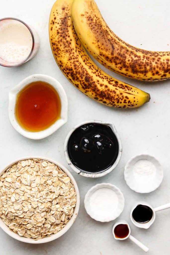 ingredients for banana black sesame tahini muffins in white bowls on a blue backdrop