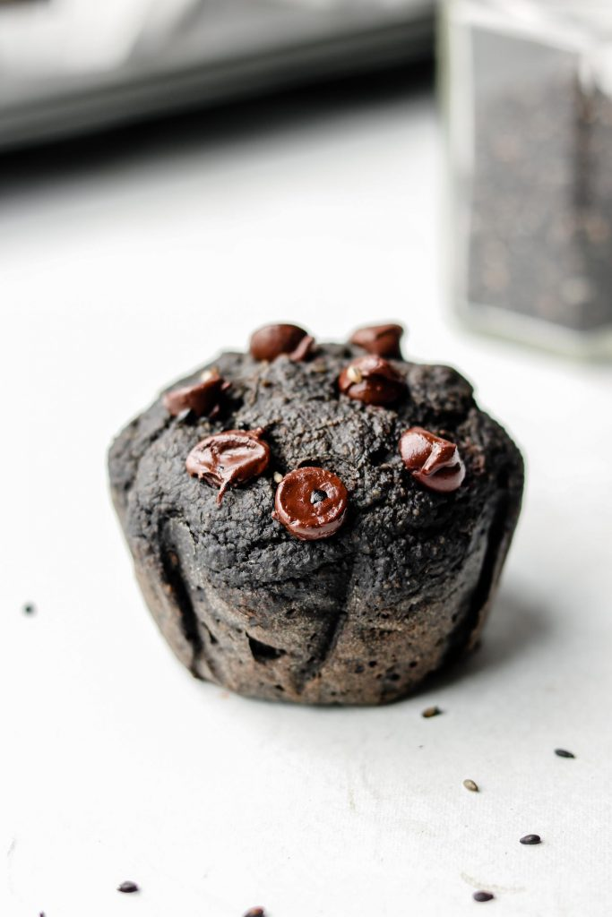 close up shot of black tahini muffins with chocolate chips on top
