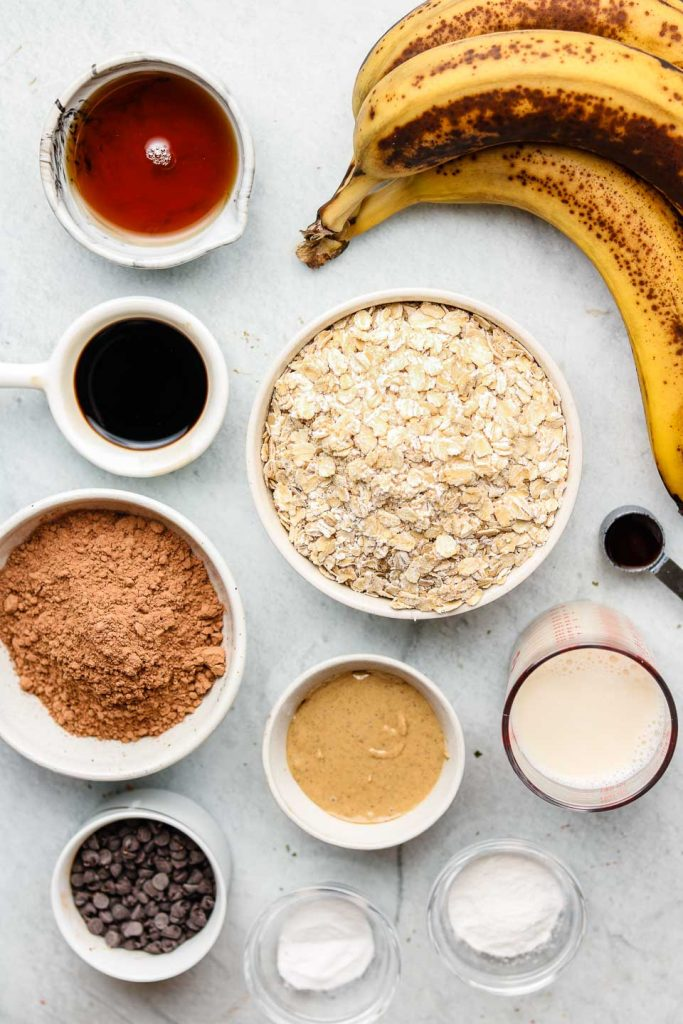 ingredients for healthy chocolate banana muffins in white bowls on a blue backdrop