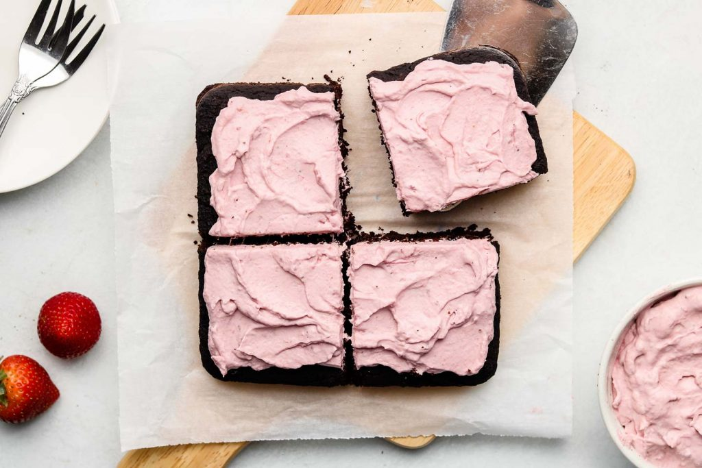 small square chocolate black sesame cake topped with strawberry whipped cream cut into 4 squares on a wooden board
