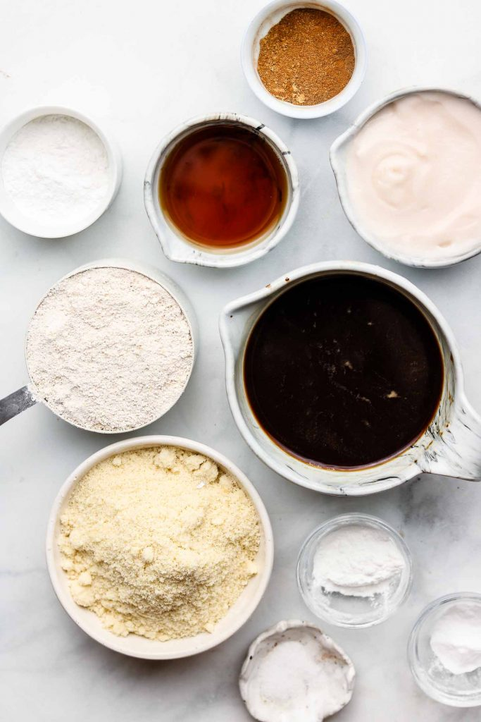 ingredients for healthy chai muffins with coffee in white bowls on a marble backdrop