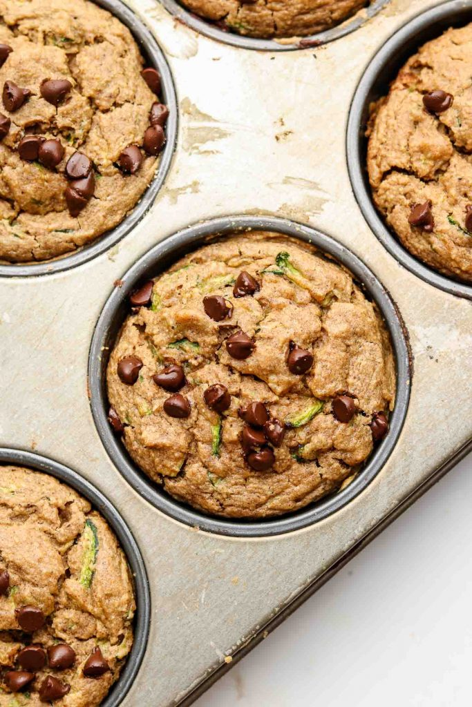 flourless vegan zucchini oat muffins in a baking pan with chocolate chips on top