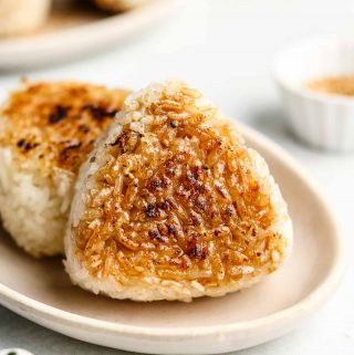 grilled japanese rice ball on a ceramic white plate with soy sauce on it