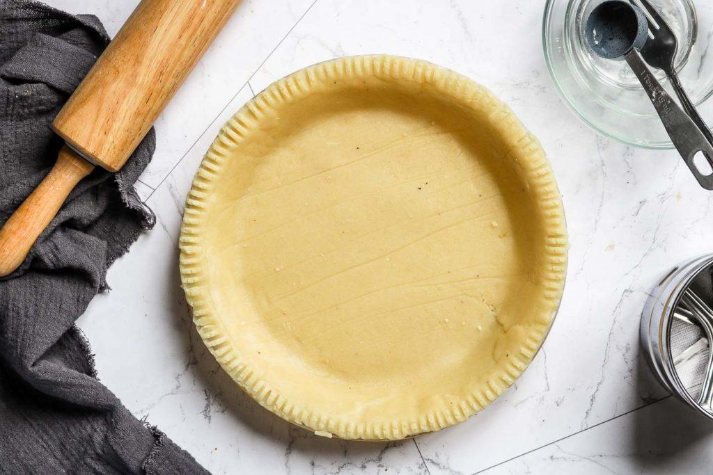 almond flour pie crust in a clear 9 inch baking dish