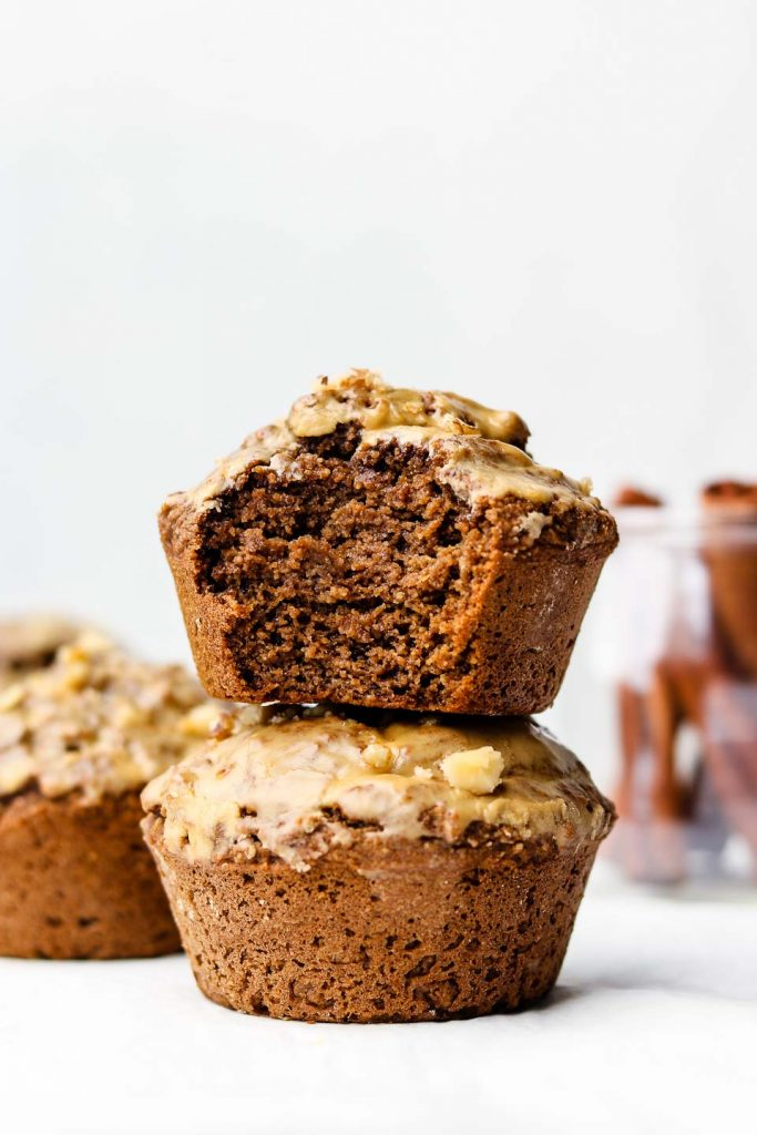 two chai muffins stacked on each other with a bite taken out of the top muffin and cinnamon sticks in a jar in the back