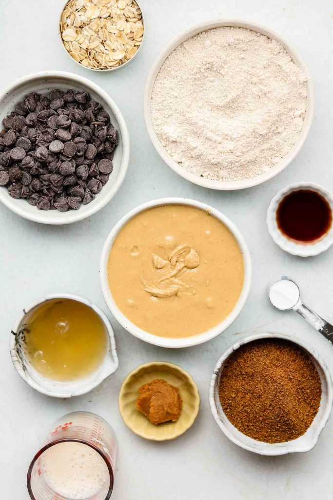 ingredients for peanut butter oatmeal cookie bars in white bowls on a blue backdrop