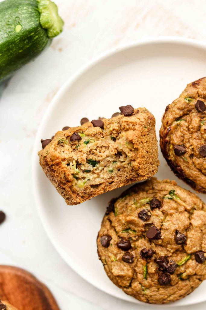 chocolate chip zucchini oat flour muffins on a white plate with a bite taken out of one of them