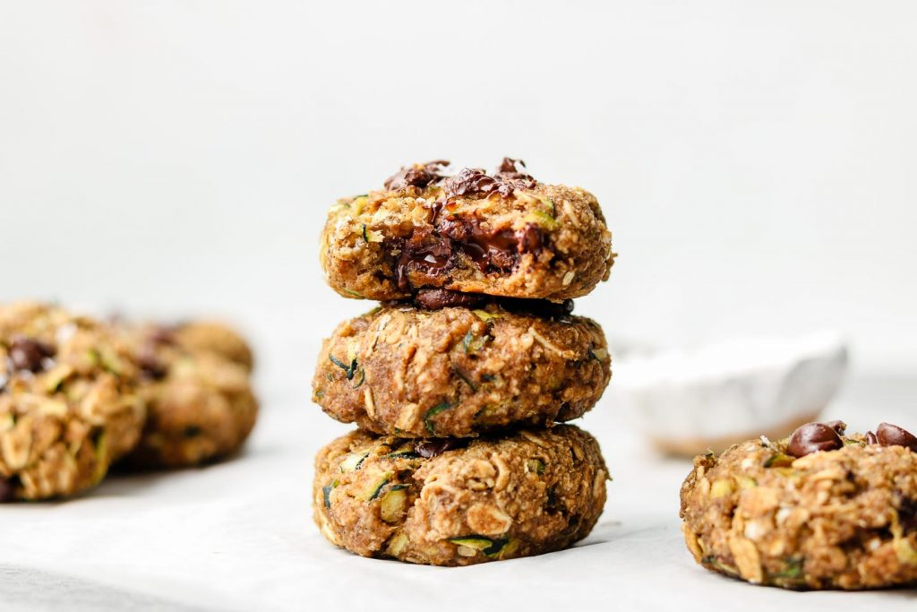 stack of eggless zucchini oatmeal cookies on parchment paper with a bite taken out of the top cookie