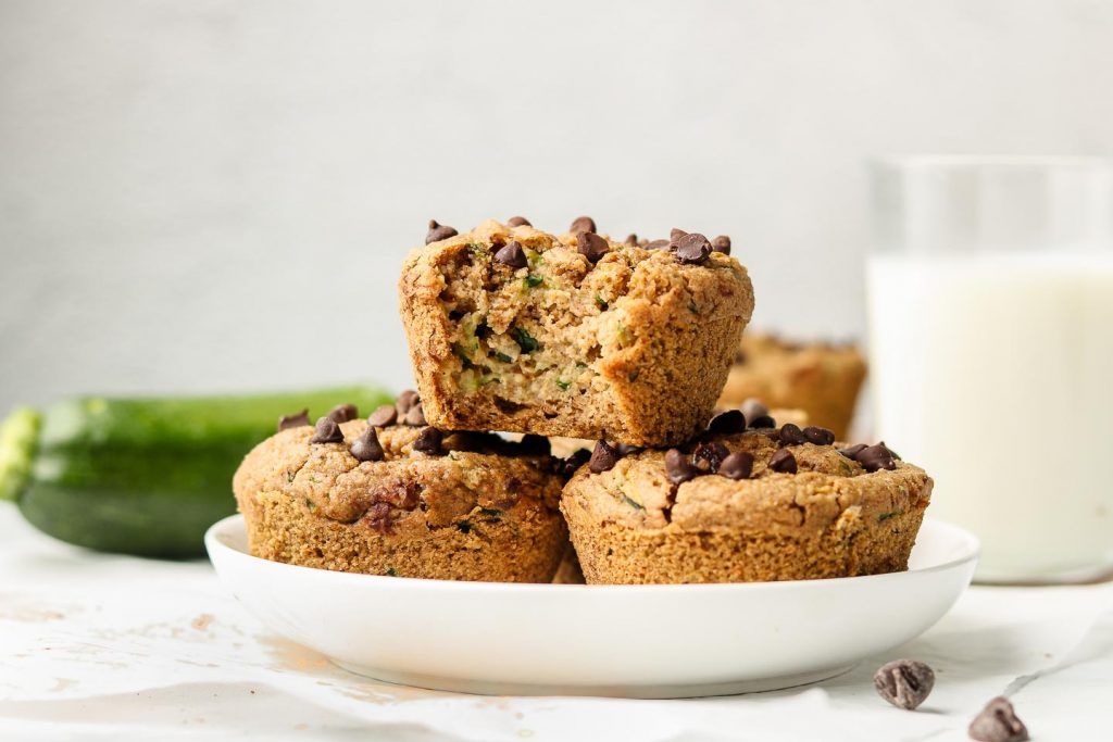 healthy zucchini muffins stacked on a white plate with milk behind it