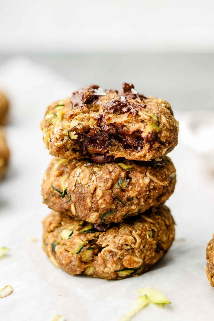 close up shot of a stack of zucchini chocolate chip oatmeal cookies with a bite taken out of the top cookie