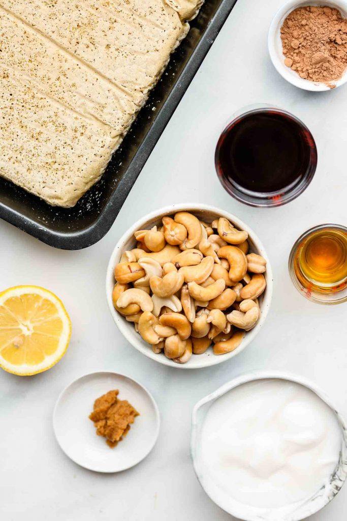 ingredients for vegan gluten free tiramisu in white bowls on a blue marble back drop