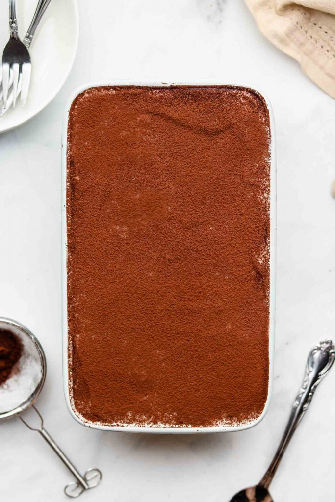 vegan dairy free tiramisu in a loaf pan with cocoa powder on top