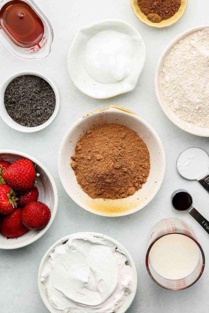 ingredients for black sesame snack cake in bowls on a blue backdrop