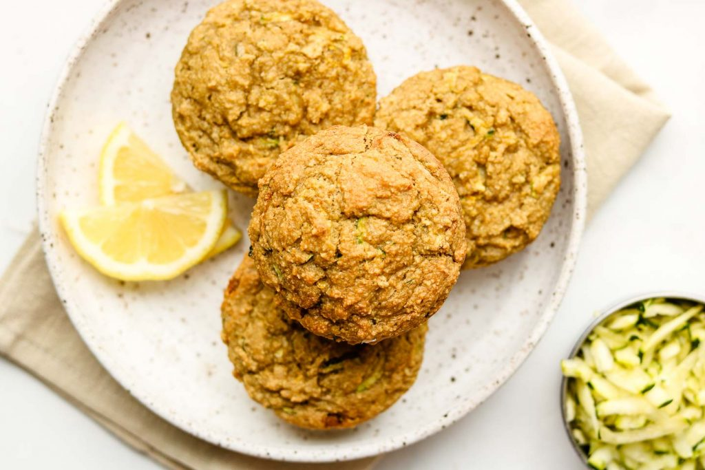 lemon zucchini muffin on a white speckled plate