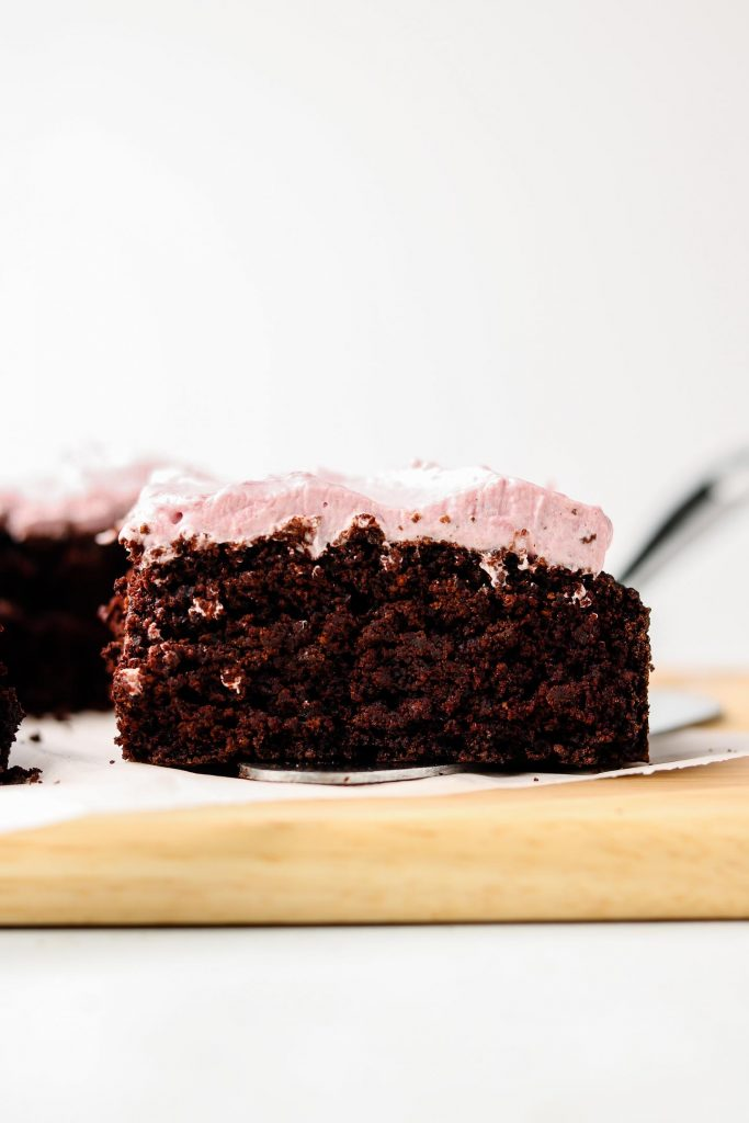 slice of chocolate black sesame cake with strawberry whip cream on a cutting board