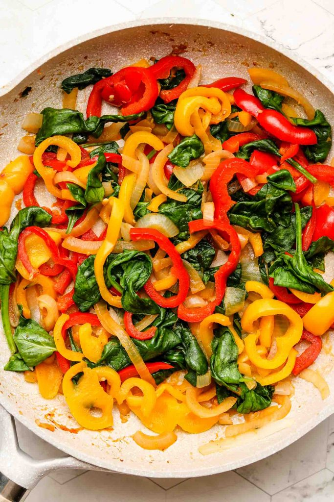 stir fried bell peppers, spinach and onions in a pink pan